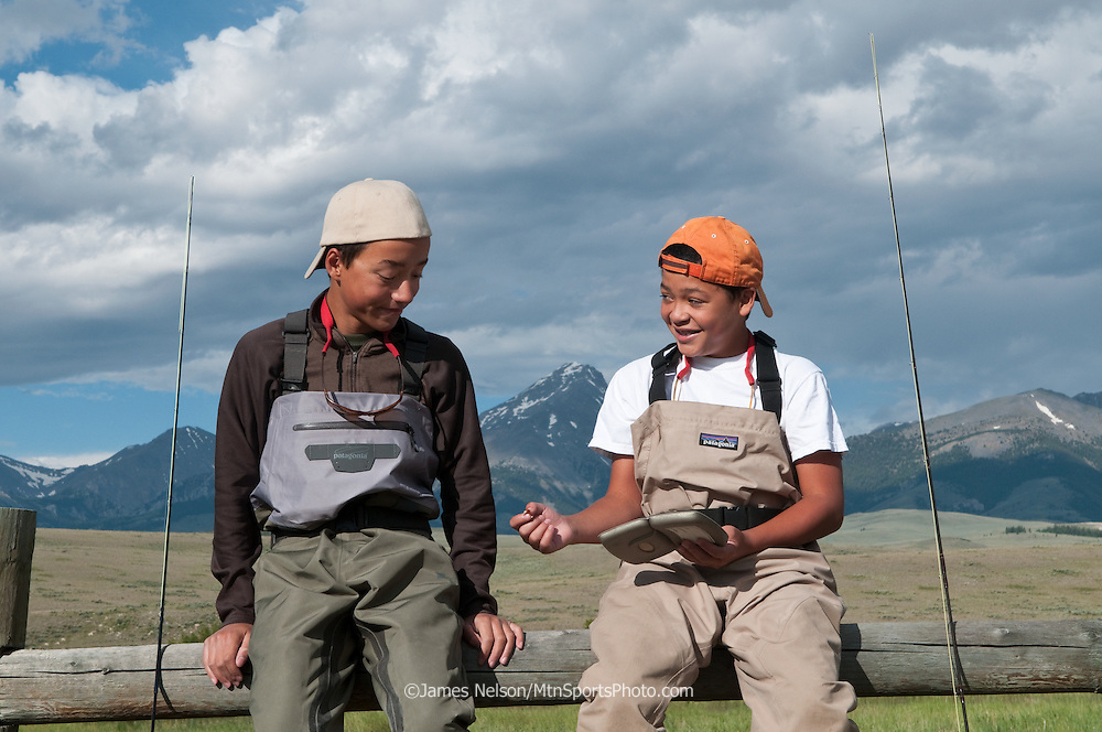 Brothers Andy and Nate Nelson (right), ages 13 and 11, discuss the finer points of fly selection while sitting on a fence near Birch Creek, a trout stream that flows along the base of the Lemhi Range in Idaho.