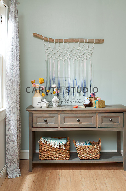Macrame wall hanging with pom-pom flowers and gift toppers on console