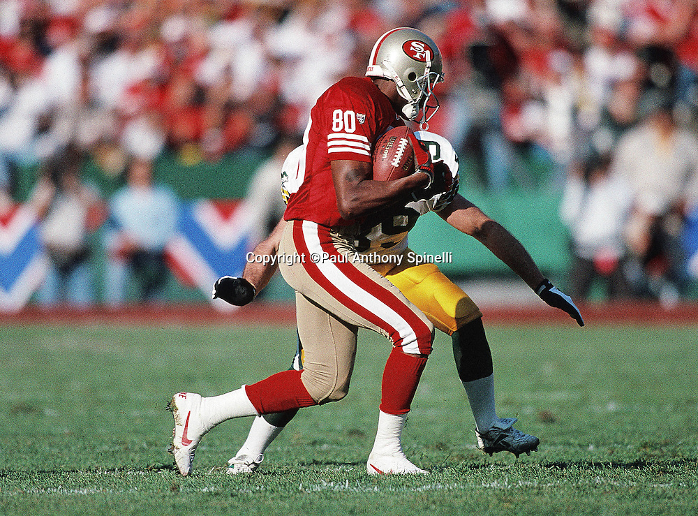 San Francisco 49ers wide receiver Jerry Rice looks to dodge a tackle by a defender after catching a pass during the NFL NFC Divisional Playoff football game against the Green Bay Packers on Jan. 6, 1996 in San Francisco. The Packers won the game 27-17. (©Paul Anthony Spinelli)