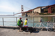 Toeristen op de fiets kijken naar de Golden Gate brug. Tussen het Schiereiland van San Francisco en Marin County ten noorden van de metropool San Francisco ligt de Golden Gate Brug over de zeestraat Golden Gate, tussen de San Fransisco Bay en de Stille Oceaan. De brug is een van de zeven moderne wereldwonderen en is op 27 mei 1937 geopend. De tolbrug is een van de meest herkenbare symbolen van San Francisco en Californie. <br /> <br /> Tourists make a photo at the Golden Gate Bridge. Between the San Francisco Peninsula and Marin County north of the metropolis of San Francisco's lays Golden Gate Bridge on the Golden Gate strait, between San Francisco Bay and the Pacific Ocean. Lies The bridge is one of the seven modern wonders of the world and was opened on May 27, 1937. The toll bridge is one of the most recognizable symbols of San Francisco and California.