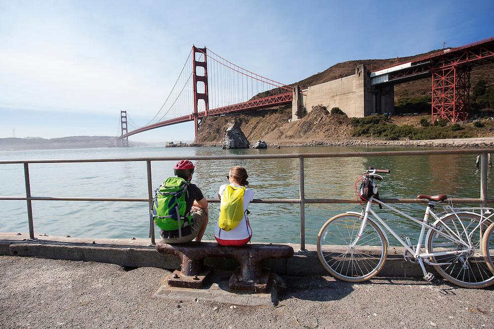 Toeristen op de fiets kijken naar de Golden Gate brug. Tussen het Schiereiland van San Francisco en Marin County ten noorden van de metropool San Francisco ligt de Golden Gate Brug over de zeestraat Golden Gate, tussen de San Fransisco Bay en de Stille Oceaan. De brug is een van de zeven moderne wereldwonderen en is op 27 mei 1937 geopend. De tolbrug is een van de meest herkenbare symbolen van San Francisco en Californie. <br /> <br /> Tourists make a photo at the Golden Gate Bridge. Between the San Francisco Peninsula and Marin County north of the metropolis of San Francisco's lays Golden Gate Bridge on the Golden Gate strait, between San Francisco Bay and the Pacific Ocean. Lies The bridge is one of the seven modern wonders of the world and was opened on May 27, 1937. The toll bridge is one of the most recognizable symbols of San Francisco and California.