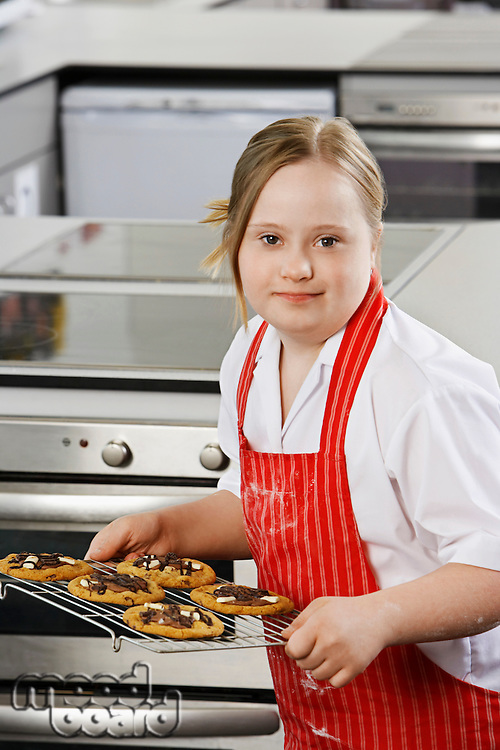 Portrait of girl (10-12) with Down syndrome carrying cookies on baking sheet