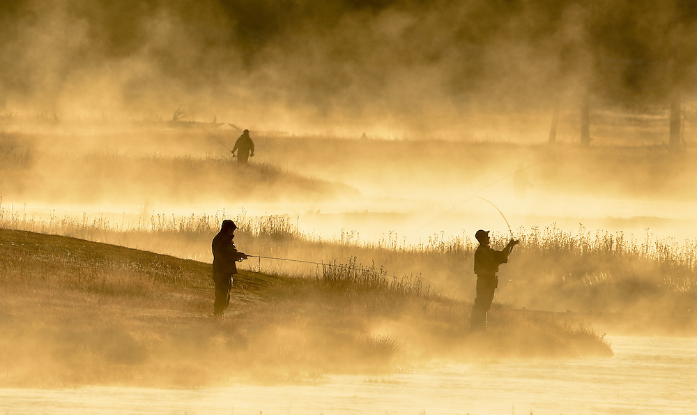 Fishermen in the early morning golden mist fish on the Madison river in Yellowstone National Park