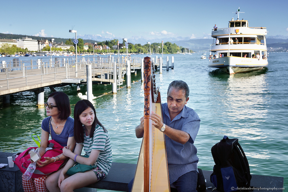 Street artist and asian tourists at the public transportation boat station at Bürkliplatz (Zürich) at Lake Zürich Shore, Switzerland