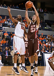 Virginia forward Jamil Tucker (12) leaps to block a jump shot by Brown center Stefan Kaluz (50).  The Virginia Cavaliers defeated the Brown University Bears 74-50 in NCAA Basketball at the John Paul Jones Arena on the Grounds of the University of Virginia in Charlottesville, VA on January 6, 2009.