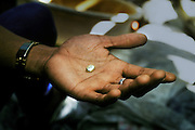 Miner holding a small nugget of gold with a value of $5 after processing 50 kilos of ore. Mount Diwata, Mindanao, The Philippines.