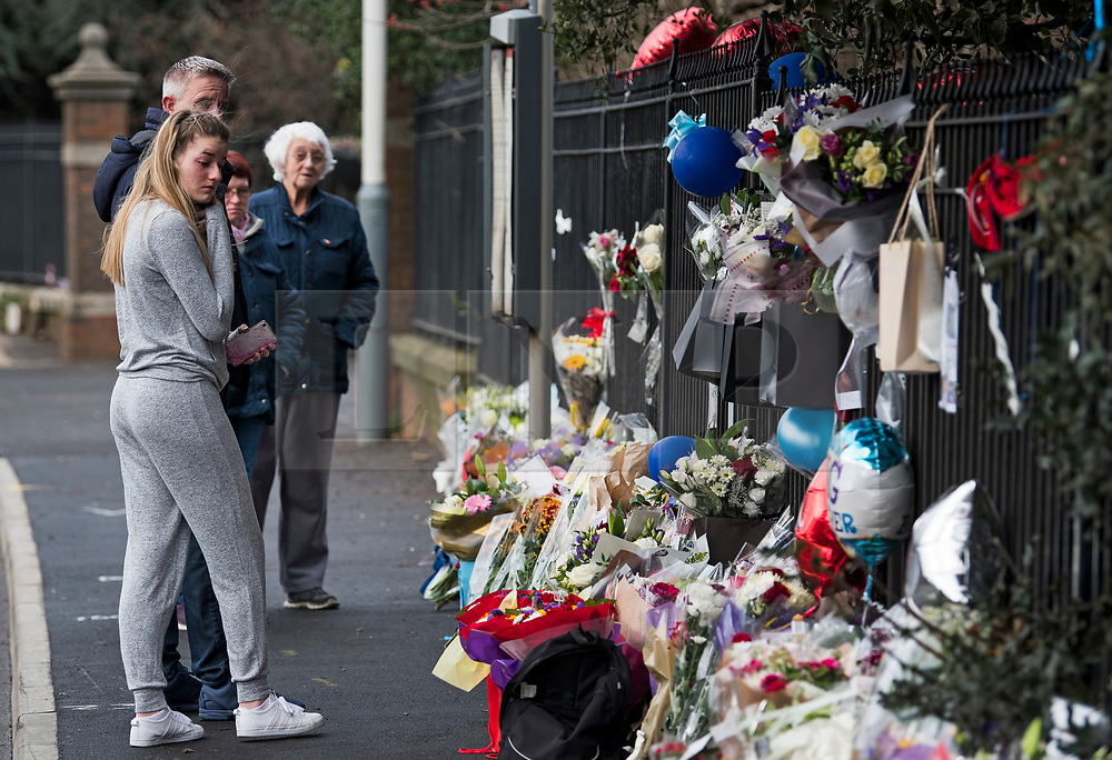 © Licensed to London News Pictures. 28/01/2018. London, UK. A group of people look at flowers placed at the scene where three teenage pedestrians were killed near a bus stop in Hayes, West London when a black Audi collided with them. Named locally as Harry Rice, Josh Kennedy and George Wilkinson, the three teenagers were hit on Friday night  close to the M4 Junction 4. A 28-year-old man has been arrested and a police are currently looking for a  second man believed to have been in the Audi.. Photo credit: Ben Cawthra/LNP