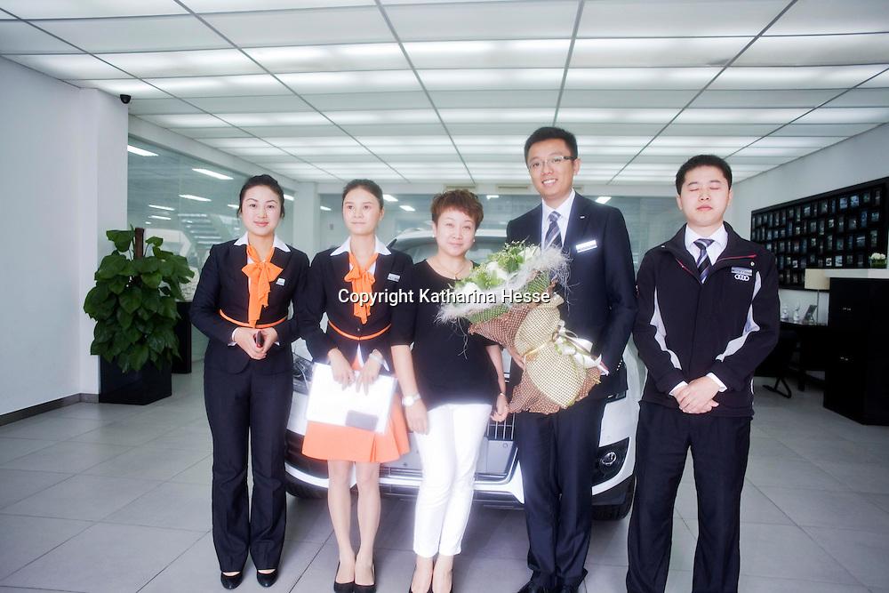 CHENGDU, 10/17/2012 :  Geschaeftsfrau Yang Xi, 37, posiert fuer ein obligatorisches Kundenfoto mit Autoangestellten.