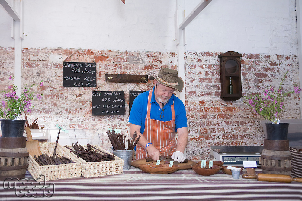 Mature man prepares speciality sausages