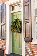 A green wooden door on a historic home decorated with a Christmas wreath on Tradd Street in Charleston, SC.