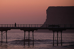 © Licensed to London News Pictures. <br /> 09/05/2016. <br /> Saltburn by the Sea, UK.  <br /> <br /> A man walks along the pier at first light at Saltburn by the Sea in North Yorkshire. After the warmest day of the year yesterday temperatures are due to drop slowly over the rest of the week.<br /> <br /> Photo credit: Ian Forsyth/LNP