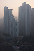 High rise accommodation blocks in downtown Shanghai glow golden as the afternoon sun penetrates the aerial pollution that cloaks the city