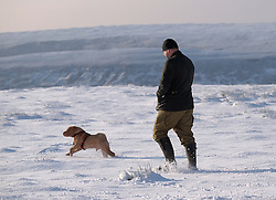 &copy; Licensed to London News Pictures. <br /> 27/12/2014. <br /> <br /> Castleton, United Kingdom.<br /> <br /> A man walks his dog across a field on the North Yorkshire Moors near Castleton after overnight snowfall caused disruption in some parts of the country.<br /> <br /> Photo credit : Ian Forsyth/LNP