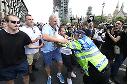 © Licensed to London News Pictures. 14/07/2018. London, UK. Supporters of US President Donald Trump and EDL founder Tommy Robinson ( real name Stephen Yaxley-Lennon ) and anti fascist demonstrations clash in Westminster . Trump is currently in Scotland and Robinson is in HMP Hull . Photo credit: Joel Goodman/LNP