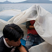 Men on the water taxi from San Pedro to San Marcos, Lago de Atitlan, Guatemala. July 2009.  (Photo/William Byrne Drumm)