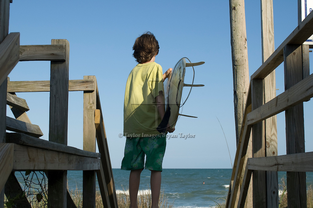 Young surfer boy surveys the waves from the boardwalk access in Myrtle Beach, South Carolina.