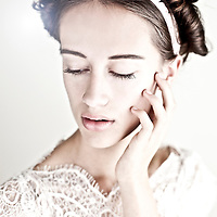 Young girl with brunette hair wearing white party dress looking down with hand to face