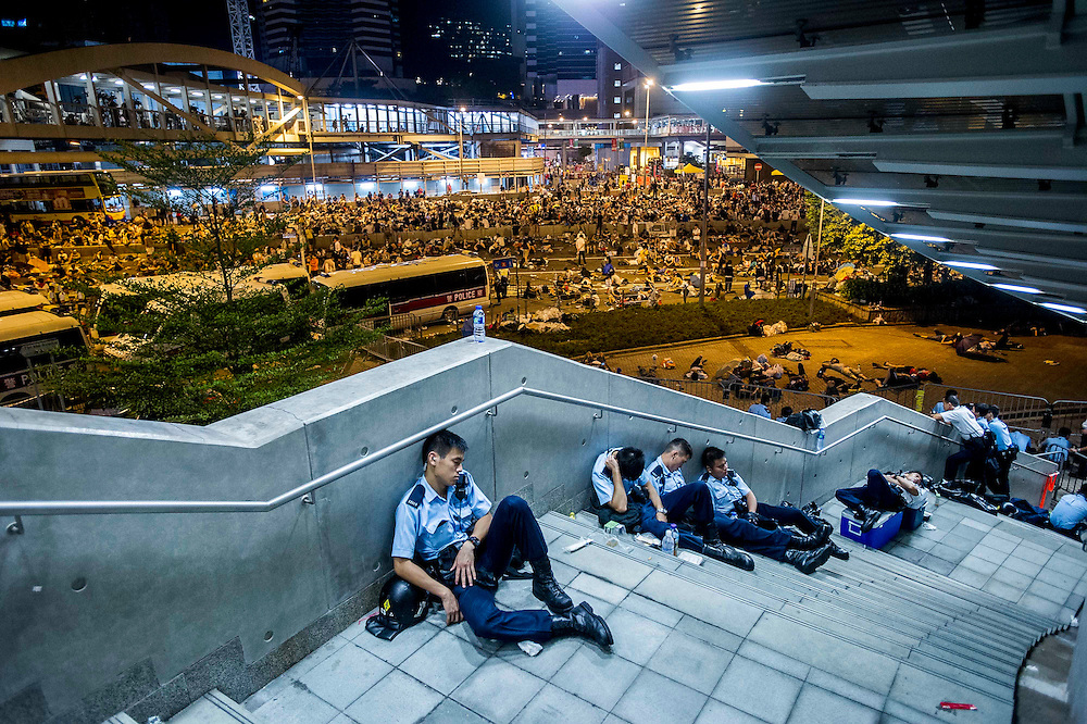 Policemen take a rest after the riots that followed a pro-democracy protest in Hong Kong on September 28, 2014. Police fired tear gas as tens of thousands of pro-democracy demonstrators brought parts of central Hong Kong to a standstill in a dramatic escalation of protests that have gripped the semi-autonomous Chinese city for days. AFP PHOTO / XAUME OLLEROS