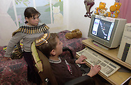 Merav Jacobi 11, left, wearing a belt of spent machine gun cartridges collected outside of her home, looks on as her brother Omer Jacobi 10, play games on the computer  Monday Dec. 4, 2000.