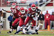 FAYETTEVILLE, AR - NOVEMBER 22:  Alex Collins #3 of the Arkansas Razorbacks is tackled from behind during a game against the Ole Miss Rebels at Razorback Stadium on November 22, 2014 in Fayetteville, Arkansas.  The Razorbacks defeated the Rebels 30-0.  (Photo by Wesley Hitt/Getty Images) *** Local Caption *** Alex Collins