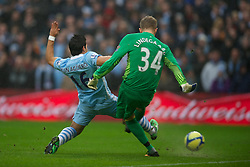 MANCHESTER, ENGLAND - Sunday, January 8, 2012: Manchester City's Sergio Aguero tackles Manchester United's goalkeeper Anders Lindegaard during the FA Cup 3rd Round match at the City of Manchester Stadium. (Pic by David Rawcliffe/Propaganda)