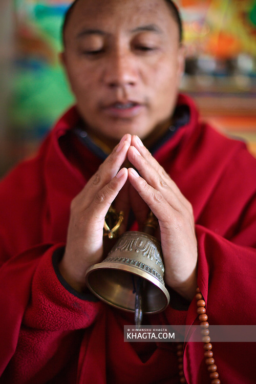 A buddhist monk in the holy town of Rewalsar in Mandi, Himachal Pradesh, India praying with his hands joined together