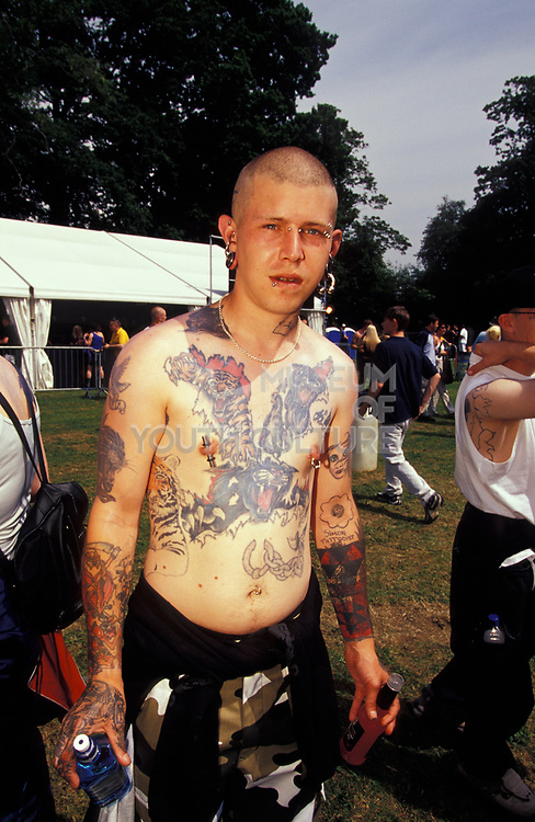 A man with shaved head and tattoo-covered torso, U.K, 2000s.