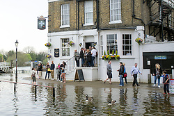 © Licensed to London News Pictures. 30/03/2014. Richmond, UK. People leave and arrive at the The White Cross pub at the high tide entrance. The high tide on the River Thames causing flooding in Richmond this afternoon 30th March 2014. Photo credit : Stephen Simpson/LNP