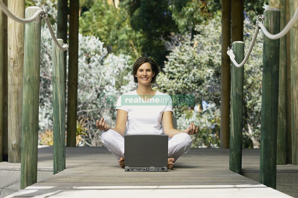 Dec. 05, 2012 - Woman with computer doing yoga (Credit Image: © Image Source/ZUMAPRESS.com)