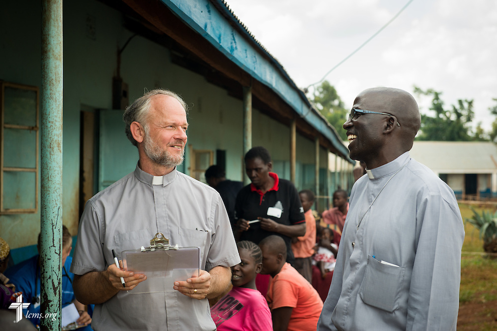 The Rev. Dr. John Juedes (left), pastor of Messiah Lutheran Church in Highland, Calif., talks to a pastor of the Evangelical Lutheran Church in Kenya during the Mercy Medical Team clinic Thursday, June 12, 2014, at the Luanda Doho Primary School in Kakmega County, Kenya. LCMS Communications/Erik M. Lunsford