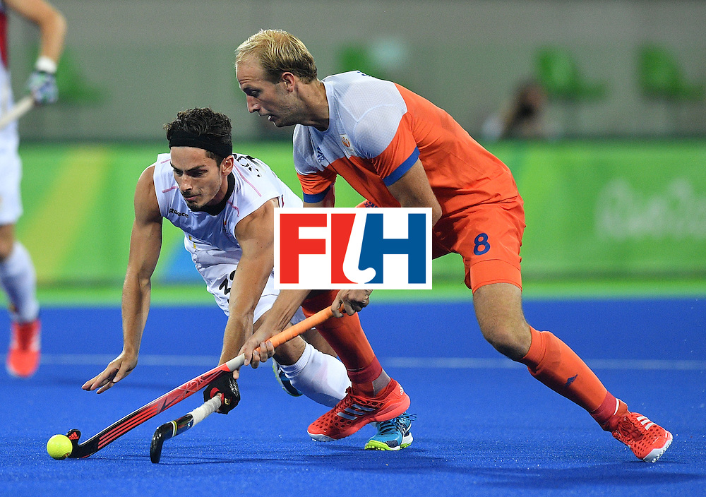 Belgium's Tanguy Cosyns (L) vies with Netherland's Billy Bakker during the men's semifinal field hockey Belgium vs Netherlands match of the Rio 2016 Olympics Games at the Olympic Hockey Centre in Rio de Janeiro on August 16, 2016. / AFP / Carl DE SOUZA        (Photo credit should read CARL DE SOUZA/AFP/Getty Images)