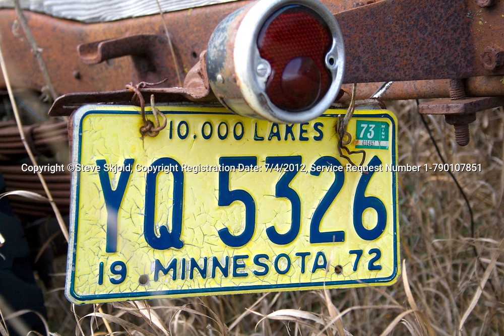 License plate from 1972 hanging on a dilapidated old truck on a farmer's field. Ottertail Minnesota MN USA
