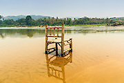 23 APRIL 2014 - CHIANG KHONG, CHIANG RAI, THAILAND: An empty chair sits in the Mekong River at a beach near Chiang Khong. Chiang Rai province in northern Thailand is facing a drought this year. The 2014 drought has been brought on by lower than normal dry season rains. At the same time, closing dams in Yunnan province of China has caused the level of the Mekong River to drop suddenly exposing rocks and sandbars in the normally navigable Mekong River. Changes in the Mekong's levels means commercial shipping can't progress past Chiang Saen. Dozens of ships are tied up in the port area along the city's waterfront.              PHOTO BY JACK KURTZ