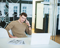 Handsome young businessman using smart phone in office