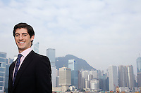 Portrait of young business man smiling office buildings in background