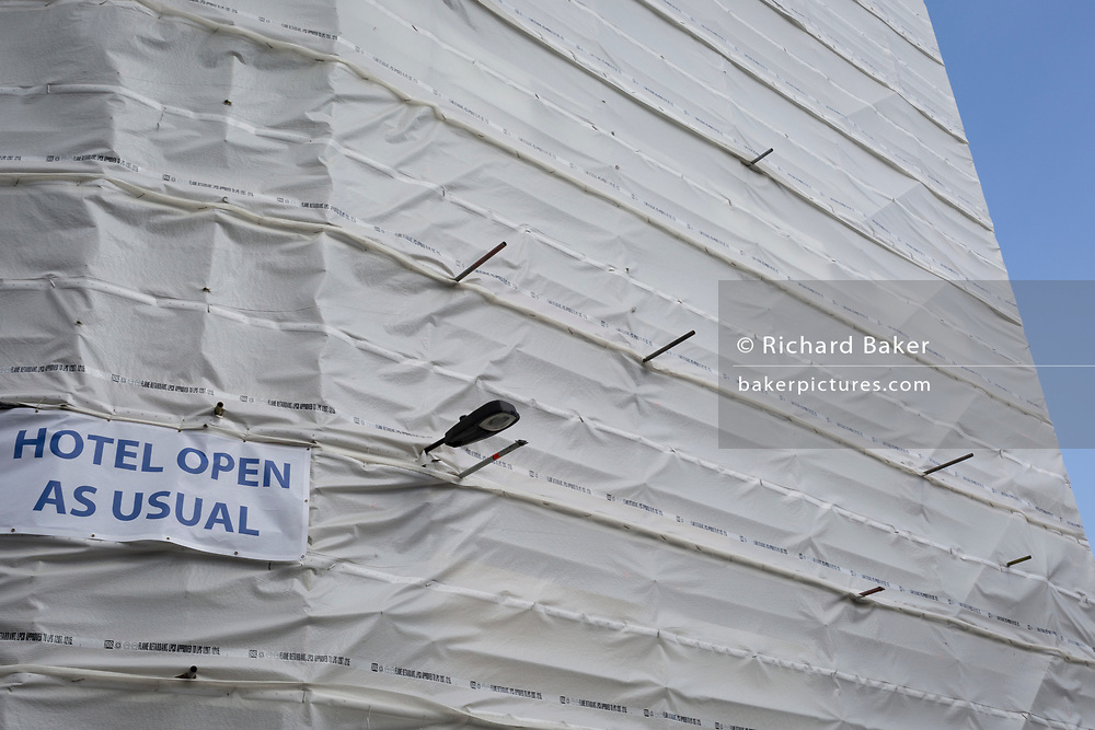 Sheeting covers the exterior of a Holiday Inn which is still managing to remain open in the borough of Southwark, on 14th May 2017, in London, England.