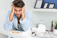 Young ill man suffering from headache at kitchen counter