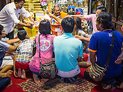 """21 JULY 2013 - BANGKOK, THAILAND:   A family makes merit and presents a senior monk with alms at Wat Mahabut on the first day of Vassa, the three-month annual retreat observed by Theravada monks and nuns. On the first day of Vassa (or Buddhist Lent) many Buddhists visit their temples to """"make merit."""" During Vassa, monks and nuns remain inside monasteries and temple grounds, devoting their time to intensive meditation and study. Laypeople support the monastic sangha by bringing food, candles and other offerings to temples. Laypeople also often observe Vassa by giving up something, such as smoking or eating meat. For this reason, westerners sometimes call Vassa the """"Buddhist Lent.""""       PHOTO BY JACK KURTZ"""