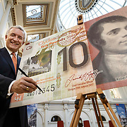 """FREE PICTURES:  <br /> <br /> CEO, David Duffy signs Clydesdale Bank's first £10 polymer note.<br /> <br /> Clydesdale Bank Chief Executive Officer, David Duffy, marked this year's Burns Night celebrations by signing the Bank's first £10 polymer note, which features Scotland's much-loved Bard. The polymer note will go into production later this year and be ready for circulation in 2017. The new note will continue to feature Robert Burns on the front with the reverse displaying views of Edinburgh, including the Castle.<br />  <br /> After signing the new note David Duffy said: """"It's a very exciting time for Clydesdale Bank and signing the new £10 note featuring Robert Burns underpins our commitment to building a strong stand-alone bank based here in Scotland that can provide a real challenge to the big UK banks. It's a privilege to see my signature alongside his portrait.""""<br />  <br /> Clydesdale Bank is the largest issuer by volume of notes in Scotland. It introduces around £400 million worth of new notes every year and in 2015 reached the milestone of having more than £2 billion worth of notes in circulation on a single day. Clydesdale Bank introduced the first fully polymer bank note to Great Britain in March 2015.<br />  <br /> Picture Robert Perry 20th Jan 2016<br /> <br /> Must credit photo to Robert Perry<br /> <br /> Image is free to use in connection with the promotion of the above company or organisation. 'Permissions for ALL other uses need to be sought and payment make be required.<br /> <br /> <br /> Note to Editors:  This image is free to be used editorially in the promotion of the above company or organisation.  Without prejudice ALL other licences without prior consent will be deemed a breach of copyright under the 1988. Copyright Design and Patents Act  and will be subject to payment or legal action, where appropriate.<br /> www.robertperry.co.uk<br /> NB -This image is not to be distributed without the prior consent of the copyright holder.<br /> i"""