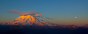 The dramatic golden light of sunset bathes the southwest face of Mount Rainier as the full moon rises over the Tatoosh Range in this panoramic view from the summit of High Rock.