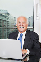 Portrait of happy elderly businessman with laptop sitting at table