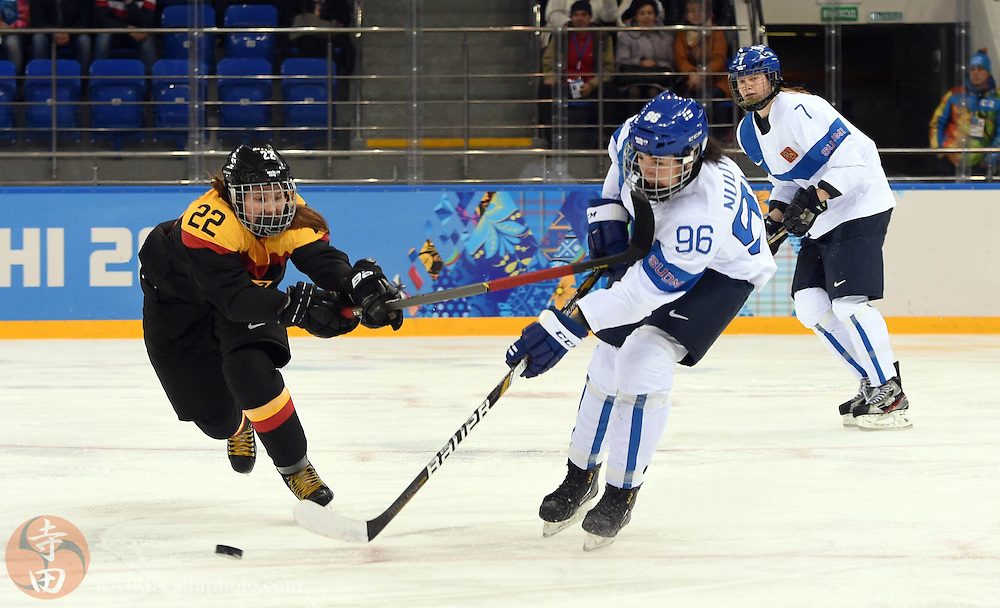 Feb 16, 2014; Sochi, RUSSIA; Finland forward Emma Nuutinen (96) reaches for the puck against Germany forward Kerstin Spielberger (22) in the women's ice hockey classifications round during the Sochi 2014 Olympic Winter Games at Shayba Arena.