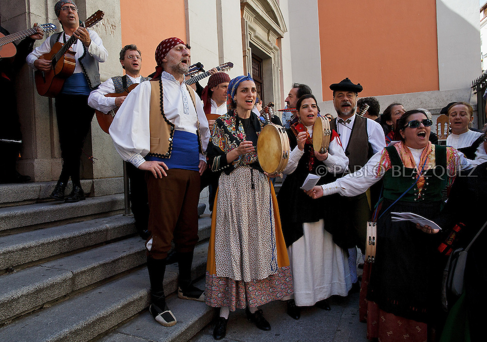 'Mayas' and 'Mayos' cerebrate the 'La Maya' tradition in the streets around the San Lorenzo church on May 10, 2015 in Lavapies neighborhood, Madrid, Spain. 'La Maya' festivity is a pagan tradition to celebrate the beginning of the spring which is believed to come from the medieval age. In old times the 'Maya's Festival' used to take place at The 'Mayas' field' (Prado de las Mayas) which is where now the San Lorenzo church is located. La Maya combines symbols of fertility and prosperity on agriculture and shepherding economy. A 'Maya' girl dressed with traditional customs sits on an altar in the street decorated with flowers, plants and cushions. Other Mayas and Mayos offer flowers, traditional sweets, lemonade, and wine to members of the public as they play music and dance. (© Pablo Blazquez)