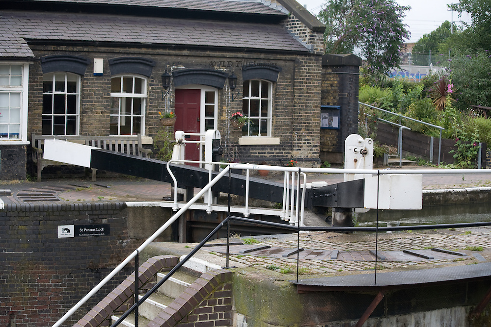 St. Pancras lock, lockhouse from across the Regent's Canal.  London.  Chilly day and nobody is around.  A vegetable garden visible beyond the 19th century lockhouse.