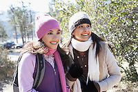 Two young women in warm clothes standing outdoors smiling.