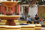 People sit in a park in the town of Valle de Angeles, Honduras on Friday April 26, 2013.