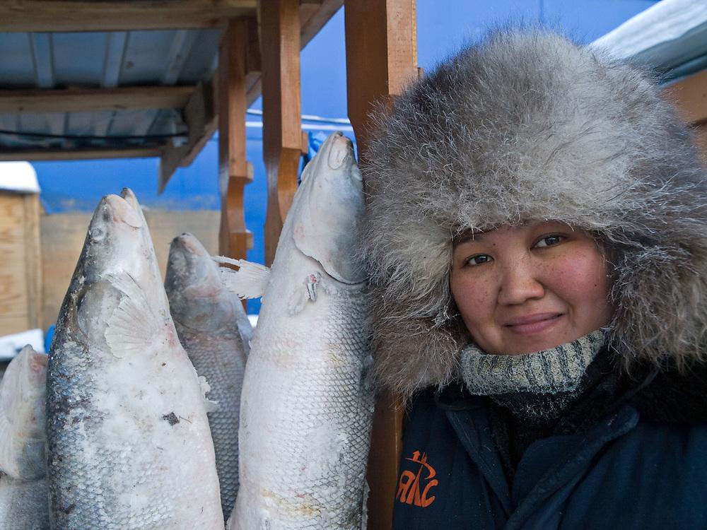 Verkaeuferin vor ihrem Stand mit tiefgefrorenen und stehenden Fischen auf dem Freiluft Markt im Zentrum von Jakutsk. Jakutsk hat 236.000 Einwohner (2005) und ist Hauptstadt der Teilrepublik Sacha (auch Jakutien genannt) im Foederationskreis Russisch-Fernost und liegt am Fluss Lena. Jakutsk ist im Winter eine der kaeltesten Grossstaedte weltweit mit durchschnittlichen Winter Temperaturen von -40.9 Grad Celsius. Die Stadt ist nicht weit entfernt von Oimjakon, dem Kaeltepol der bewohnten Gebiete der Erde.<br /> <br /> Seller in front of her stall with deep frozen and standing fishes on the Yakutsk outdoor fish market. Yakutsk is a city in the Russian Far East, located about 4 degrees (450 km) below the Arctic Circle. It is the capital of the Sakha (Yakutia) Republic (formerly the Yakut Autonomous Soviet Socialist Republic), Russia and a major port on the Lena River. Yakutsk is one of the coldest cities on earth, with winter temperatures averaging -40.9 degrees Celsius.
