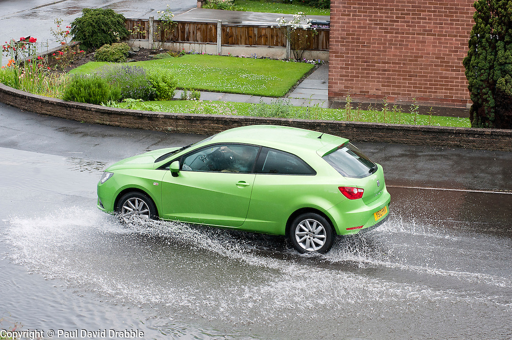 16:45 Ecclesfield Sheffield UK.One vehicle makes it way through the flood on the opposite side of the road to try and avoid the deepest part of the flood..5 July 2012.Image © Paul David Drabble
