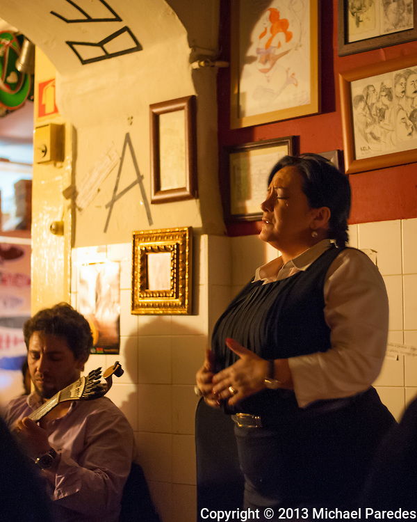 A fadista sings her soulful ballad , accompanied simply by a guitarist, in a tiny bar in Barrio Alto.