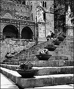 Young mother breastfeeding her child while begging for some money on the steps of the cathedral of Cefalù, Sicily, Italy.